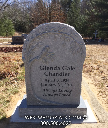 Gray granite headstone with tree and bird carving