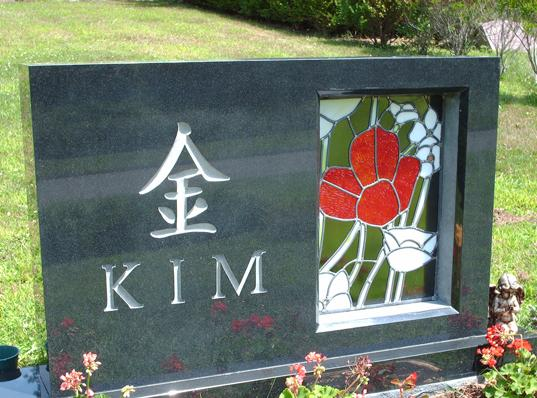 black simple headstone with beautiful floral stained glass insert