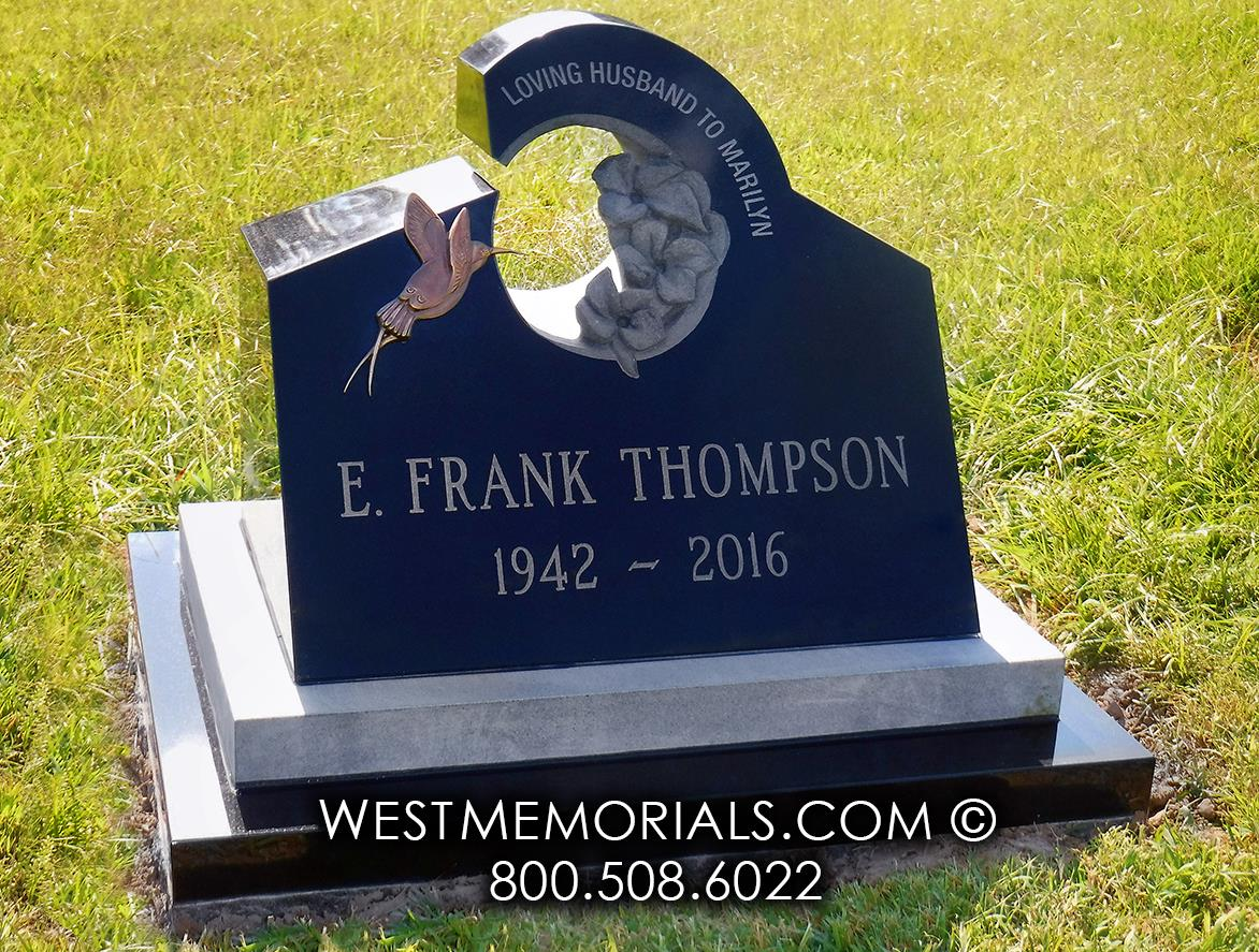 Black slant headstone with bronze hummingbird and carved flowers