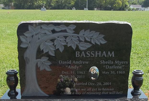 Companion black monument with carved tree and etching with flower vases by West Memorials